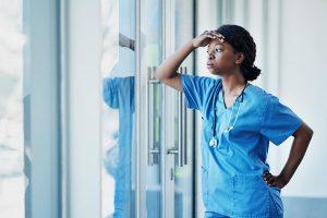 Female doctor or nurse looking stressed at work